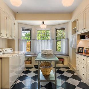 Esempio di una sala lavanderia classica di medie dimensioni con ante a filo, ante beige, top in legno, pareti beige, pavimento in legno verniciato, lavatrice e asciugatrice affiancate e top marrone