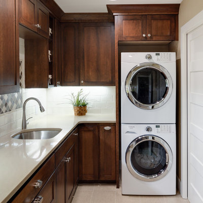 Example of a mid-sized classic l-shaped beige floor and ceramic tile dedicated laundry room design in Portland with dark wood cabinets, white countertops, an undermount sink, shaker cabinets, quartz countertops, beige walls and a stacked washer/dryer