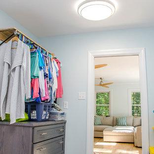 Klassisk inredning av en liten parallell tvättstuga enbart för tvätt, med luckor med lamellpanel, grå skåp, träbänkskiva, blå väggar, en tvättmaskin och torktumlare bredvid varandra, klinkergolv i keramik och beiget golv