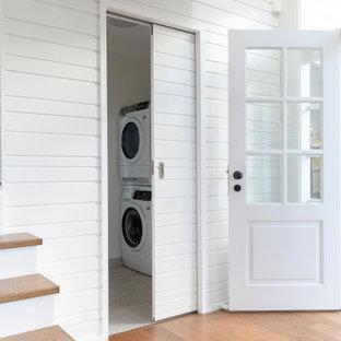 Exotisk inredning av ett mellanstort grå parallellt grått grovkök, med en undermonterad diskho, skåp i shakerstil, vita skåp, marmorbänkskiva, vita väggar, mellanmörkt trägolv, en tvättpelare och brunt golv