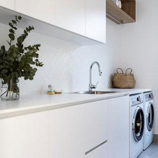 Exempel på en maritim vita parallell vitt tvättstuga, med släta luckor, vita skåp, en tvättmaskin och torktumlare bredvid varandra och grått golv