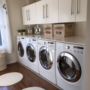 Idéer för att renovera en mycket stor funkis linjär tvättstuga enbart för tvätt, med släta luckor, vita skåp, bänkskiva i koppar, vita väggar, mörkt trägolv och en tvättmaskin och torktumlare bredvid varandra