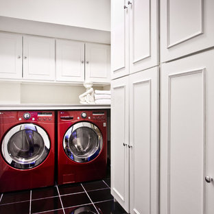 Example of a transitional black floor laundry room design in DC Metro with white cabinets and a side-by-side washer/dryer