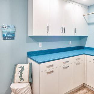 Inspiration för en mellanstor vintage blå l-formad blått tvättstuga enbart för tvätt, med en nedsänkt diskho, släta luckor, vita skåp, laminatbänkskiva, blå väggar, mellanmörkt trägolv, en tvättmaskin och torktumlare bredvid varandra och brunt golv