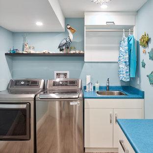 Idéer för en mellanstor klassisk blå l-formad tvättstuga enbart för tvätt, med en nedsänkt diskho, släta luckor, vita skåp, laminatbänkskiva, blå väggar, mellanmörkt trägolv, en tvättmaskin och torktumlare bredvid varandra och brunt golv