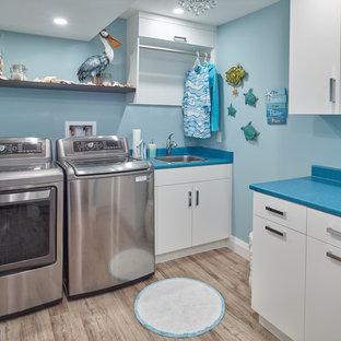 Idéer för mellanstora vintage l-formade blått tvättstugor enbart för tvätt, med en nedsänkt diskho, släta luckor, vita skåp, laminatbänkskiva, blå väggar, mellanmörkt trägolv, en tvättmaskin och torktumlare bredvid varandra och brunt golv