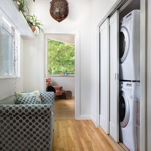 Inspiration pour une petit buanderie linéaire design avec un placard, un mur blanc, un sol en bois clair et des machines superposées.