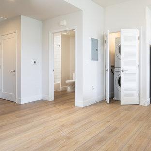 Idées déco pour une petit buanderie rétro avec un placard, des portes de placard blanches, un sol en vinyl, des machines superposées et un sol jaune.
