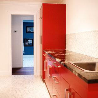Inspiration pour une buanderie parallèle minimaliste dédiée avec un évier encastré, un placard à porte plane, des portes de placard rouges, un plan de travail en granite, un mur blanc, un sol en carrelage de céramique et des machines côte à côte.