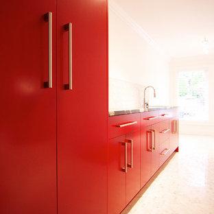 Aménagement d'une buanderie parallèle moderne dédiée avec un évier encastré, un placard à porte plane, des portes de placard rouges, un plan de travail en granite, un mur blanc, un sol en carrelage de céramique et des machines côte à côte.