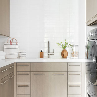 Design ideas for a mid-sized modern u-shaped dedicated laundry room in Salt Lake City with light wood cabinets, white walls, ceramic floors, a side-by-side washer and dryer, grey floor and white benchtop.
