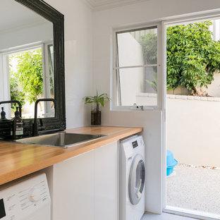Immagine di una sala lavanderia contemporanea con lavello da incasso, ante lisce, ante bianche, top in legno, pareti bianche e top marrone