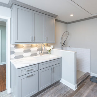 Inspiration for a small galley utility room in Cincinnati with an undermount sink, recessed-panel cabinets, grey cabinets, quartz benchtops, multi-coloured splashback, ceramic splashback, grey walls, porcelain floors, a side-by-side washer and dryer, grey floor and white benchtop.