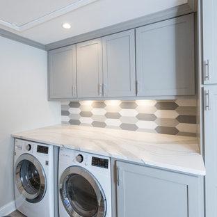 Bild på ett litet vit parallellt vitt grovkök, med en undermonterad diskho, luckor med infälld panel, grå skåp, bänkskiva i kvarts, flerfärgad stänkskydd, stänkskydd i keramik, grå väggar, klinkergolv i porslin, en tvättmaskin och torktumlare bredvid varandra och grått golv