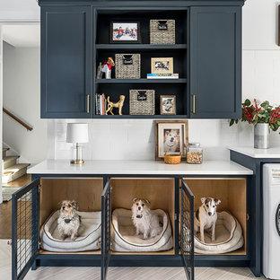 Cette image montre une buanderie rustique multi-usage avec un placard à porte shaker, des portes de placard bleues, un mur blanc et un sol beige.