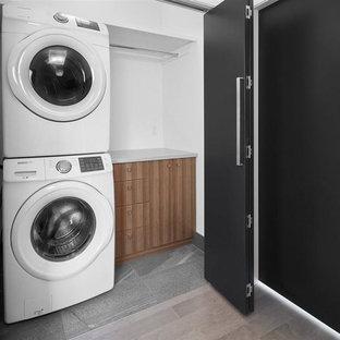 Ispirazione per un ripostiglio-lavanderia design con ante lisce, ante in legno scuro, top in quarzo composito, pareti bianche, pavimento in gres porcellanato e lavatrice e asciugatrice a colonna