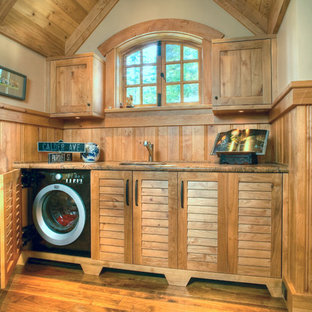 Immagine di una lavanderia classica con ante a persiana, ante in legno scuro, pareti beige e pavimento in legno massello medio