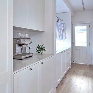 Inspiration for a mid-sized transitional galley utility room in Sydney with an undermount sink, shaker cabinets, quartz benchtops, white walls, light hardwood floors, a concealed washer and dryer and white cabinets.