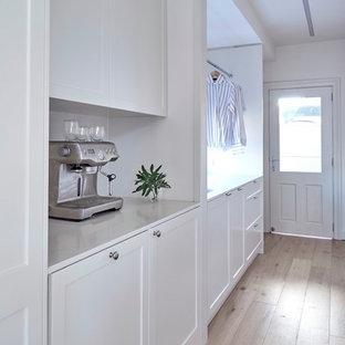 Inspiration för mellanstora klassiska parallella grovkök, med en undermonterad diskho, skåp i shakerstil, bänkskiva i kvarts, vita väggar, ljust trägolv, tvättmaskin och torktumlare byggt in i ett skåp och vita skåp