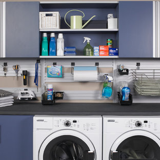 Example of a trendy single-wall laundry room design in Charlotte with flat-panel cabinets, blue cabinets, solid surface countertops, a side-by-side washer/dryer and black countertops