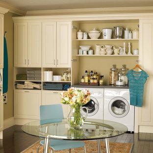 Immagine di una lavanderia multiuso classica di medie dimensioni con ante con bugna sagomata, ante beige, pareti beige, lavatrice e asciugatrice affiancate, top in quarzo composito, parquet scuro, pavimento marrone e top grigio