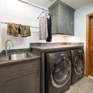 Immagine di una sala lavanderia tradizionale di medie dimensioni con lavello sottopiano, ante con riquadro incassato, ante in legno bruno, top in superficie solida, pareti blu, pavimento in gres porcellanato e lavatrice e asciugatrice affiancate