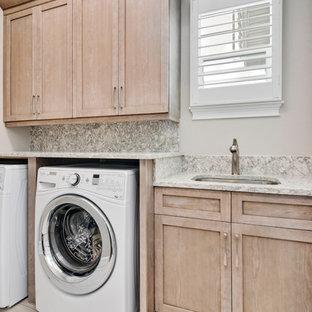 Esempio di una sala lavanderia chic di medie dimensioni con lavello sottopiano, ante in stile shaker, ante in legno chiaro, top in quarzo composito, pareti beige, pavimento in gres porcellanato, lavatrice e asciugatrice affiancate e pavimento beige