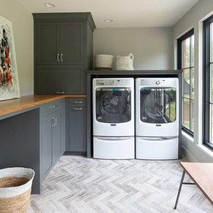Inredning av en skandinavisk bruna l-formad brunt tvättstuga enbart för tvätt, med grå skåp, träbänkskiva, klinkergolv i porslin, en tvättmaskin och torktumlare bredvid varandra, grått golv, skåp i shakerstil och grå väggar