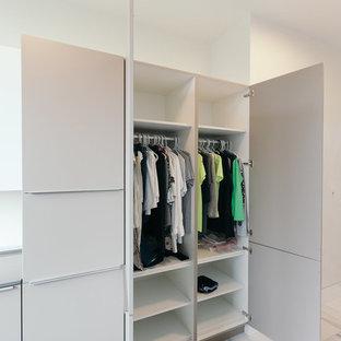Ispirazione per un'ampia sala lavanderia minimalista con lavello sottopiano, ante lisce, top in quarzo composito, paraspruzzi bianco, paraspruzzi con lastra di vetro, pavimento con piastrelle in ceramica, ante grigie e lavatrice e asciugatrice affiancate