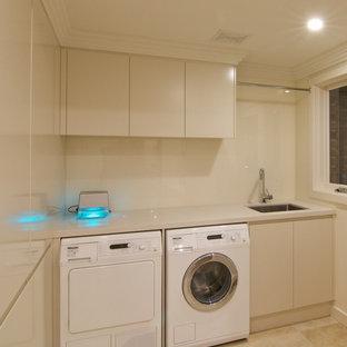 Idéer för en mellanstor modern beige parallell tvättstuga, med en undermonterad diskho, släta luckor, bänkskiva i kvarts, beige skåp, brunt stänkskydd, glaspanel som stänkskydd, travertin golv och beiget golv