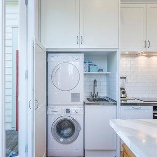 Bild på ett litet linjärt grovkök, med en allbänk, skåp i shakerstil, vita skåp, vita väggar, mellanmörkt trägolv, tvättmaskin och torktumlare byggt in i ett skåp och orange golv