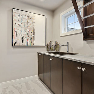 Mid-sized coastal ceramic floor and white floor dedicated laundry room photo in Other with a drop-in sink, flat-panel cabinets, brown cabinets, marble countertops, gray walls, a side-by-side washer/dryer and blue countertops