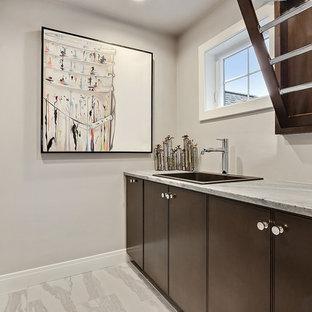 Idéer för att renovera en mellanstor maritim blå blått tvättstuga enbart för tvätt, med en nedsänkt diskho, släta luckor, bruna skåp, marmorbänkskiva, grå väggar, klinkergolv i keramik, en tvättmaskin och torktumlare bredvid varandra och vitt golv