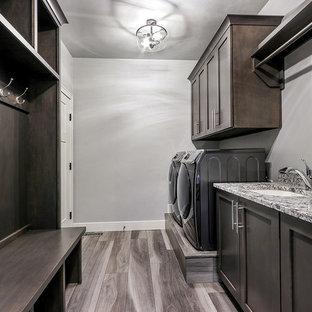Idée de décoration pour une buanderie parallèle minimaliste multi-usage avec un évier encastré, un placard à porte shaker, des portes de placard grises, un plan de travail en granite, un mur gris, un sol en vinyl, des machines côte à côte et un plan de travail multicolore.