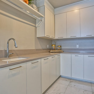 Large contemporary l-shaped separated utility room in Other with a submerged sink, flat-panel cabinets, white cabinets, engineered stone countertops, grey walls, porcelain flooring, a side by side washer and dryer, white floors and grey worktops.