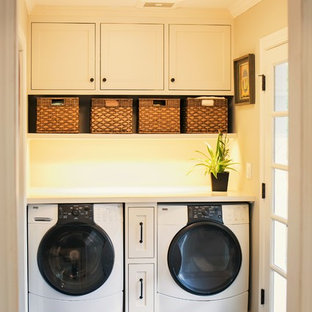 Small country single-wall laundry room in San Francisco with multi-coloured splashback, glass sheet splashback, shaker cabinets, white cabinets, a side-by-side washer and dryer, quartzite benchtops, beige walls, slate floors and black floor.