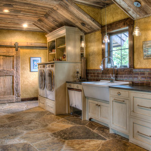 Large country galley dedicated laundry room in Minneapolis with a double-bowl sink, beaded inset cabinets, white cabinets, granite benchtops, yellow walls, slate floors, a side-by-side washer and dryer, multi-coloured floor and black benchtop.