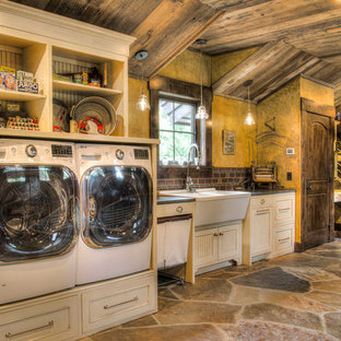 This is an example of a large rustic galley separated utility room in Minneapolis with a double-bowl sink, beaded cabinets, white cabinets, granite worktops, yellow walls, slate flooring, a side by side washer and dryer, multi-coloured floors and black worktops.
