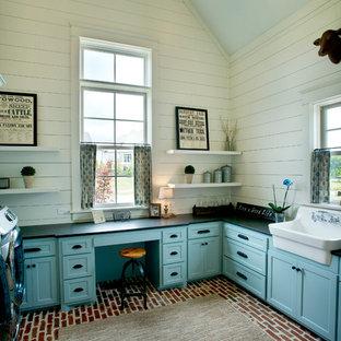 Inredning av ett lantligt u-format grovkök, med en rustik diskho, skåp i shakerstil, blå skåp, bänkskiva i täljsten, vita väggar, tegelgolv och en tvättmaskin och torktumlare bredvid varandra