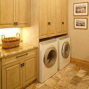 Immagine di una grande sala lavanderia classica con ante beige, top in granito, pareti beige, lavatrice e asciugatrice affiancate e ante con bugna sagomata