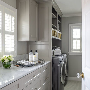 Mid-sized elegant ceramic tile and white floor dedicated laundry room photo in Austin with shaker cabinets, gray cabinets, gray walls, a side-by-side washer/dryer, marble countertops and white countertops