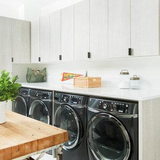 Foto på en lantlig vita l-formad tvättstuga, med släta luckor, grå skåp, vita väggar och en tvättmaskin och torktumlare bredvid varandra