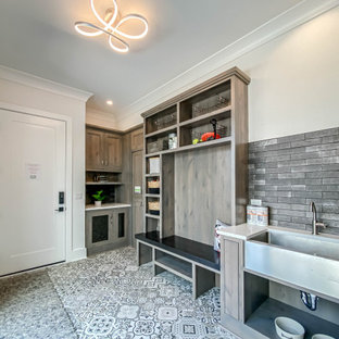 Large industrial galley utility room in Chicago with a farmhouse sink, shaker cabinets, distressed cabinets, quartz benchtops, grey splashback, brick splashback, white walls, ceramic floors, white floor, white benchtop and brick walls.