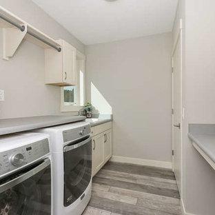 Inspiration för mellanstora moderna parallella tvättstugor enbart för tvätt, med en allbänk, luckor med infälld panel, vita skåp, grå väggar och en tvättmaskin och torktumlare bredvid varandra