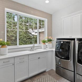 Exempel på en stor amerikansk vita l-formad vitt tvättstuga enbart för tvätt, med en undermonterad diskho, skåp i shakerstil, vita skåp, bänkskiva i kvartsit, grått stänkskydd, stänkskydd i glaskakel, vita väggar, klinkergolv i keramik, en tvättmaskin och torktumlare bredvid varandra och grått golv