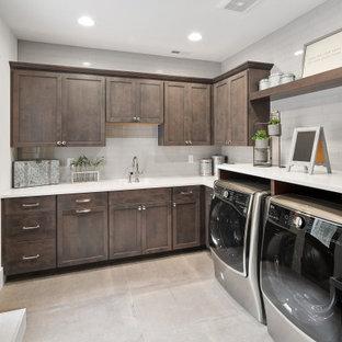 Idéer för att renovera en stor amerikansk vita l-formad vitt tvättstuga enbart för tvätt, med en undermonterad diskho, skåp i shakerstil, skåp i mörkt trä, bänkskiva i kvartsit, grått stänkskydd, stänkskydd i glaskakel, vita väggar, klinkergolv i keramik, en tvättmaskin och torktumlare bredvid varandra och grått golv
