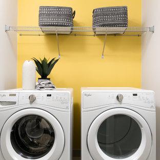 Inredning av en modern liten tvättstuga, med gula väggar och en tvättmaskin och torktumlare bredvid varandra