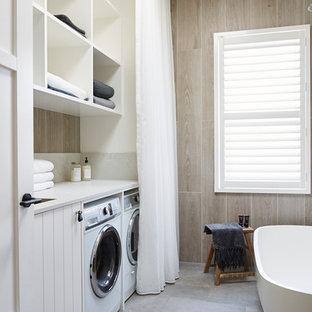 Modern inredning av ett mellanstort grå parallellt grått grovkök, med en nedsänkt diskho, öppna hyllor, vita skåp, bänkskiva i kvarts, bruna väggar, klinkergolv i porslin, en tvättmaskin och torktumlare bredvid varandra och grått golv