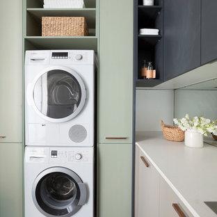 Ispirazione per una sala lavanderia moderna di medie dimensioni con lavello da incasso, ante lisce, ante nere, top in quarzo composito, pareti bianche e lavatrice e asciugatrice a colonna