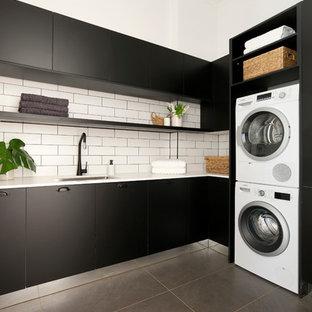 Inspiration för mellanstora moderna l-formade tvättstugor enbart för tvätt, med en nedsänkt diskho, släta luckor, svarta skåp, bänkskiva i kvarts, vita väggar och en tvättpelare